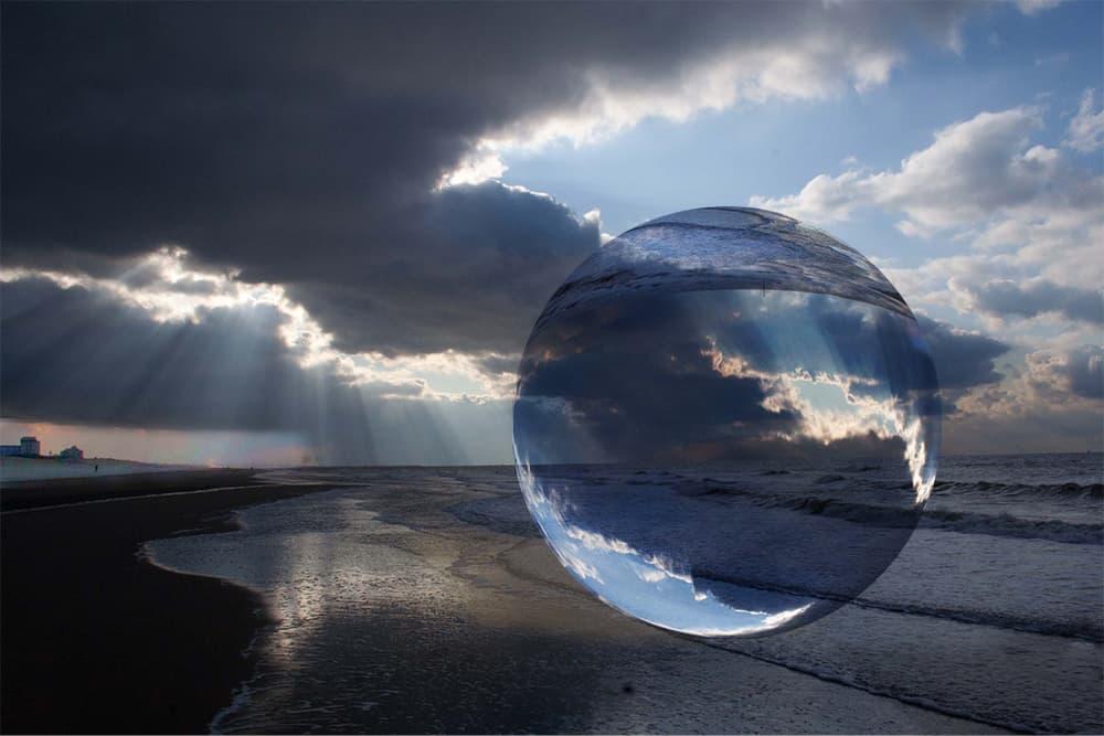 Foto van de kustlijn van scheveningen waarboven een transparante bol zweeft die de omgeving weerkaatst