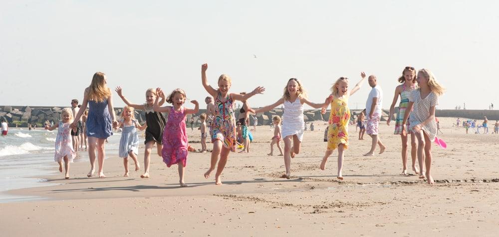 Kinderen rennen en juichen naast elkaar al rennend op het strand.